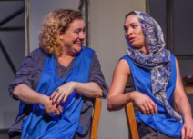 Photo of two women, both wearing blue aprons, sitting down facing each other