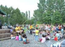 Photo of children and families sitting in Hulme Park watching a theatre performance