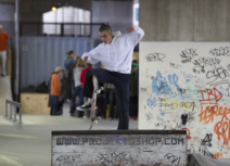 Man in white hoodie making a jump on a skateboard from a ramp