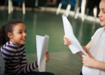 Photo of two children holding pieces of A4 paper and looking at each other smiling
