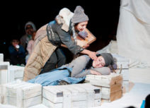 Production image for 'Where's My Igloo Gone?'. A woman wearing a grey hat and jumper using a blue coat as a blanket is leaning on white coloured wooden crates. Another woman wearing a grey beanie hat and beige and black coat and is leaning over her as though trying to wake her up.
