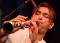 A close-up photo of a man with dark hair and a white t-shirt playing a clarinet.