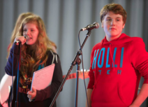 Photo of a teenage girl and boy. The girl is stood on the left and is wearing a navy jumper, she has long blonde hair. The boy is wearing a red 'Hollister' jumper and has short brown hair. Both children are standing behind microphones.