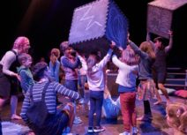Production image from The Chit Chat Chalk Show. Children and actors are holding large black foam cubes which have been drawn on with blue chalk