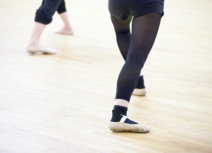 Promotional image for Contemporary Ballet. Picture of a pair of child's legs wearing black tights and ballet pumps.