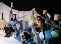 Production photo of Where's My Igloo Gone? An actor in a blue coat is holding up a piece of paper, the audience is sat to her right, looking at her and also holding up pieces of paper.