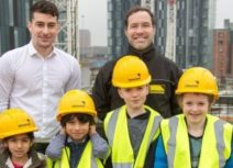 Photo of four children and two adults on Renaker development viewing platform. The children are wearing yellow hi-vis jackets and yellow hard hats.