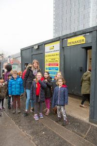 Photo of children on visit to Renaker construction site. They are standing in front of a black static caravan with a yellow 'Renaker' sign on it.