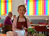 Picture of child smiling directly at the camera, she is wearing a pink jumper and a red apron. In the foreground are paint brushes, egg boxes and other arts and crafts supplies. In the background are rainbow coloured window blinds.