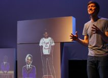 Production image from Friends For All. A man is standing in front of projected images of children who are wearing school uniform, one child is stood on a table wearing a white t-shirt that says 'fight the power' on it),