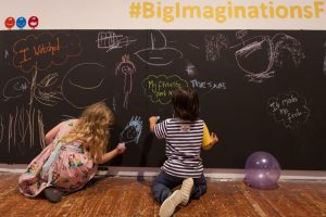 Children drawing on a blackboard at Big Imaginations festival