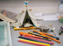 Picture of a small teepee tent made of push pins, beige fabric and pencils. The toy tent is behind a pile of coloured pencil crayons.
