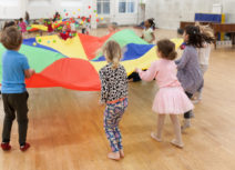 Picture of a group of 4 - 6 year olds standing in a circle holding a multi-coloured parachute. There are small multi-coloured balls bouncing on the parachute and the children are stood on a wooden, laminate floor.