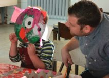 A child wearing a stripey top and red apron is holding a paper plate mask in front of his face, a man in a blue shirt is sat next to him looking at him.