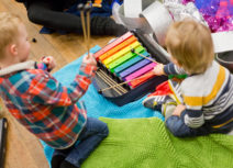 Two pre-school aged children are sat on green and blue mats playing on a rainbow coloured xylophone.