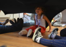 A girl wearing a white vest top, purple lanyard and red trousers is sitting underneath a black cloth held up by other children and an adult