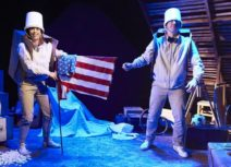 Production shot - One Small Step. A man and a woman dressed in beige are wearing buckets on their heads. The woman is holding an american flag and they are both wearing cardboard boxes as though they are rucksacks