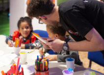 A man and two children doing art activities. The man is stood up and the two children are sitting down at a table. On the table are felt tip pens, pencil crayons, pieces of paper and plastic cups filled with coloured tissue paper.