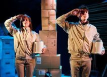 One Small Step production image. A man and a woman dressed in beige are facing forward and saluting. In the background is a tower made of cardboard boxes.