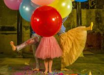 Promotional photo for Tidy Up. Photo of three people holding large red, yellow, green, pink and blue balloons, only their legs are visible.
