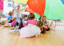 Children aged 4 - 6 playing under multi-coloured parachute