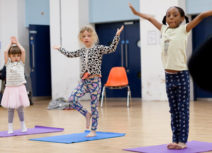 Three young girls are standing on yoga mats and holding their arms up in the air.