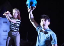 One Small Step Production photo. In the foreground a man with short dark hair wearing a blue shit and black bow tie is holding up a black and blue football. Behind him a woman in a black and white striped tshirt is holding a toy spaceship.