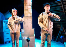 One Small Step production image. A man and a woman dressed in beige are facing forward, zipping up their jackets in unison. In the background is a tower made of cardboard boxes.
