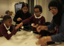 Picture of schoolchildren and teachers constructing a shape out of white marshmallows and wooden sticks.