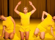 Picture of three dancers wearing yellow t-shirts and shorts