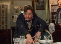 Production image from INUK. An older man is frantically setting a table in the foreground, behind him, a younger man wearing a navy coat and a yellow beanie hat is watching him with a puzzled expression on his face.