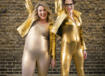 Promotional photo for Scummy Mummies. Two women are dressed entirely in gold spandex, both have one arm raised in the air.
