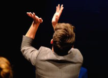 A man with short brown hair wearing a grey blazer is facing away from the camera and clapping into the air.