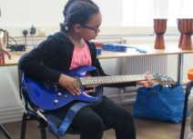A girl is sat wearing a black cardigan, pink tshirt and black leggings playing a blue electric guitar.
