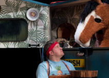 Production photo from Black Beauty. A man holding a bucket wearing a red headband and blue tshirt is looking up at a brown and white pantomime horse who is inside a blue horsebox.