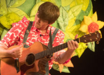 Production Image - Climb That Tree. Man with short brown hair playing a guitar and wearing dungarees and a red and white patterned shirt.
