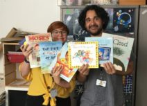 Photo of Z-arts development manager Gemma, and Finance and Administration Officer Ramsey holding children's books donated from Amazon Wishlist