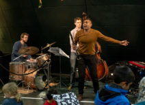 Picture of three musicians performing to a group of children in Z-arts cafe. At the front is Arun Ghosh who has short black hair, is wearing a brown jumper and is holding a clarinet. Behind him is a man in a grey shirt and jeans playing a double bass and to his left is a man wearing glasses and a dark blue jumper playing on a bronze coloured drum set.