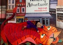 Book cover of 'Nimesh the Adventurer'. Cartoon image of a red and orange dragon with green feet, there is a girl wearing blue with brown boots riding its back and holding onto its ears.