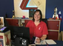 Picture of a member of box office staff wearing a red Z-arts t-shirt Z-arts' front desk