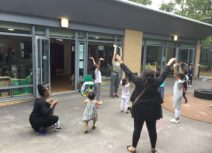 Parents and children dancing together outside. They are all holding their hands up in front of the air and are standing in front of a school building in a playground