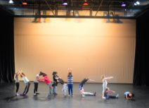 A group of children stand in Z-arts' theatre space spelling out the word 'dance' with their bodies