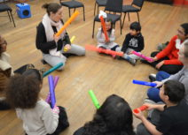 A group of children and adults are sat cross-legged on the floor in a circle, they are all holding different brightly-coloured plastic tubes.