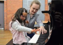 A girl approximately 6 years old is sitting at a piano. She is wearing a grey polkadot jumper and a light pink stripey gilet. Next to her is an adult female wearing a black and white stripey shirt