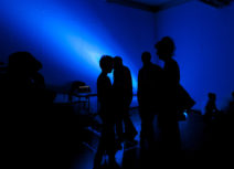 Group of people of silhouetted by dark blue light