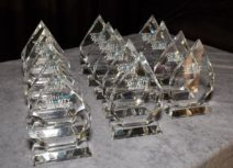 Photo of 15 North West Charity Award trophies lined up on a table with a grey velvet tablecloth