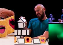 Collage of three production images from 'a square world'. 1st image, 1 spherical yellow sponge with a mouth shape and two yellow cube sponges with a mouth shape. Middle photo, man with blue tshirt and beard performing with the sponges. 3rd photo, zoomed out photo of the set showing that the performance is happening on a glowing green desk