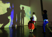 Photo of children dancing in front of wall projections