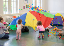 Children playing with giant, multicoloured sheet, launching different coloured balls into the air