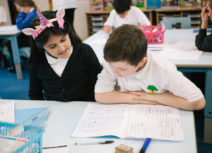 A young girl and a young boy working together, looking at a creative writing book
